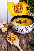 Cream pumpkin soup with fresh herbs and crackers on dark