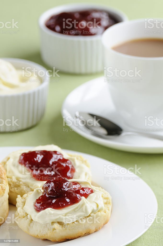 Cream with jam on biscuits with tea stock photo