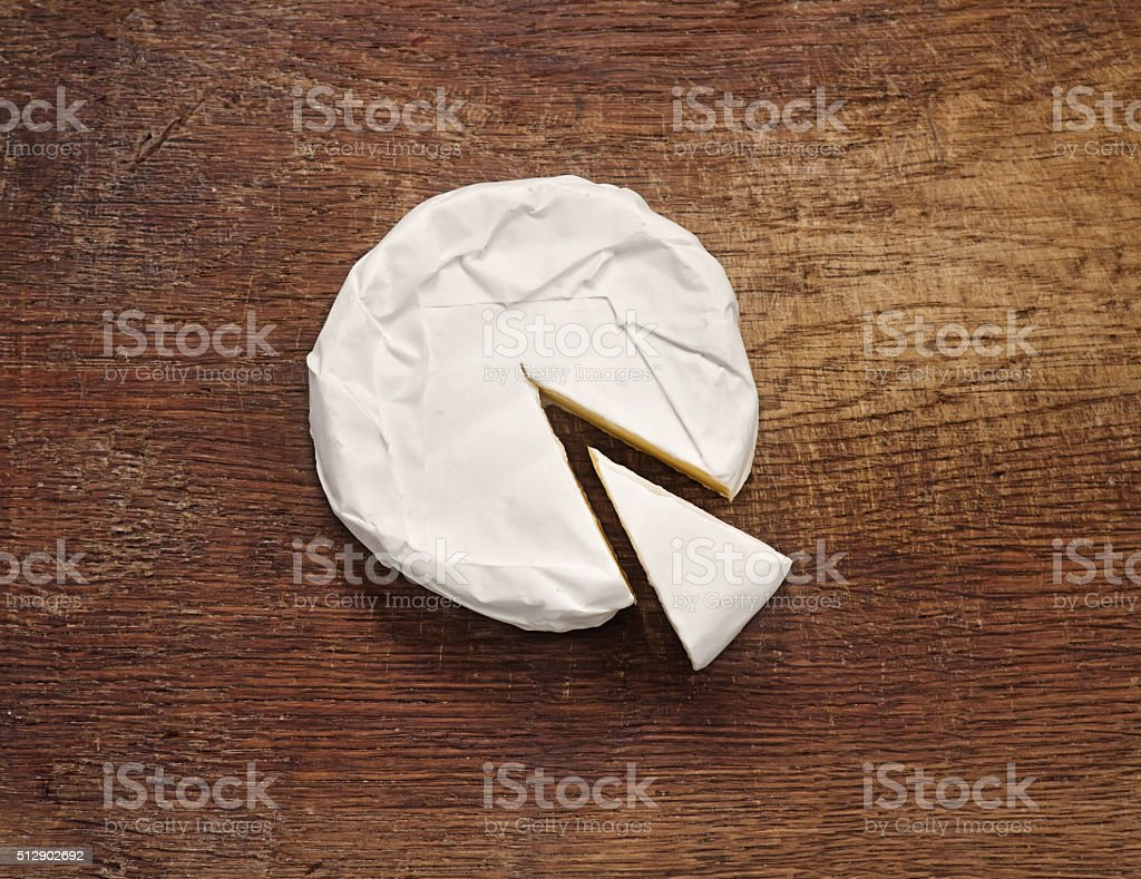 Creamy Brie on rustic wooden background stock photo