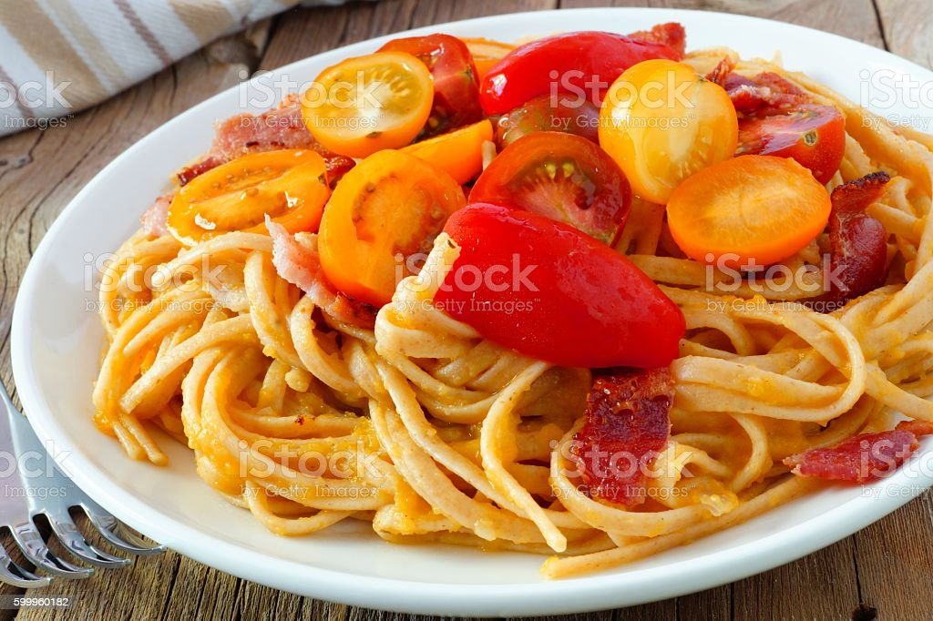 Creamy butternut squash pasta with bacon and cherry tomatoes close-up stock photo