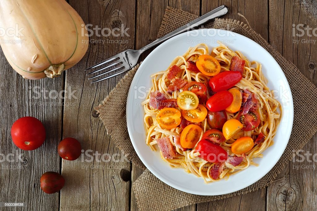 Creamy butternut squash pasta with bacon and tomatoes over wood stock photo