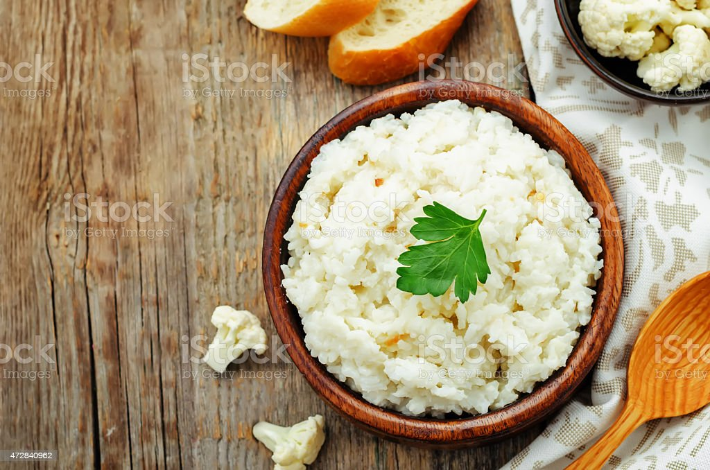 Creamy cauliflower garlic rice in a bowl on a wooden table stock photo