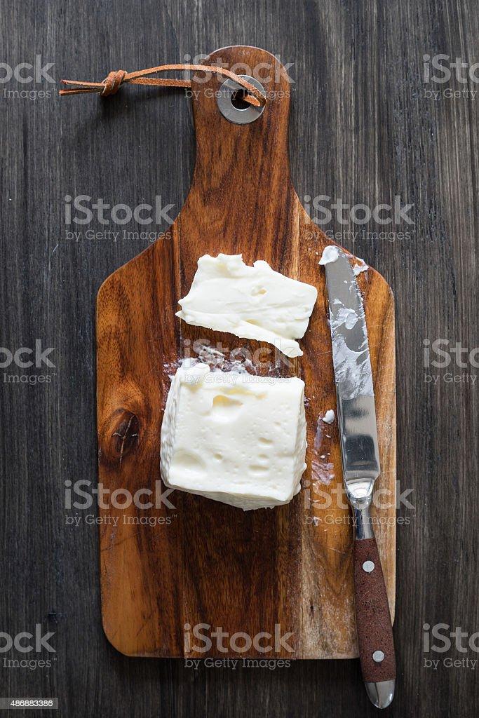 Creamy italian Stracchino cheese on the wooden cutting board stock photo