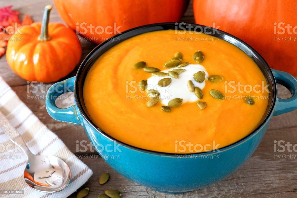 Creamy pumpkin soup in a blue bowl close up stock photo