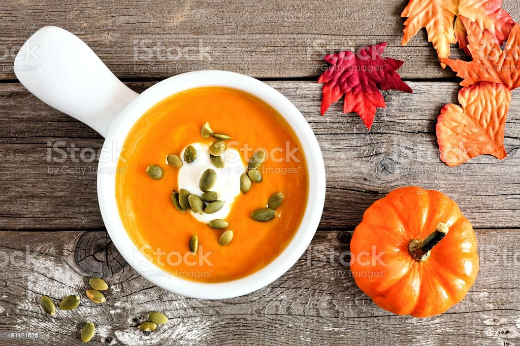 Creamy pumpkin soup on rustic wood background stock photo
