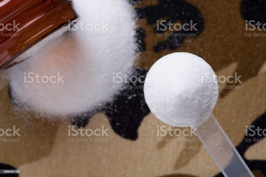 Creatine Micronized on a camouflage background stock photo