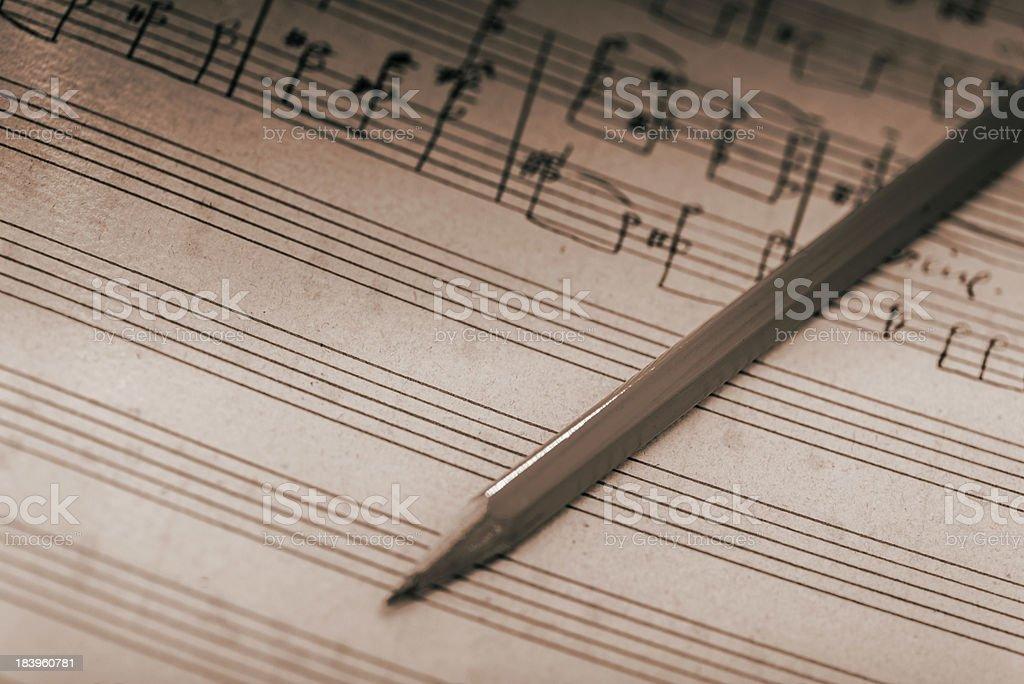 Creating music: pencil on pentagram stock photo