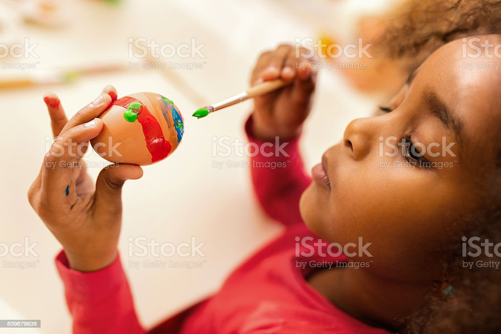 Creative African American little girl painting Easter egg. stock photo