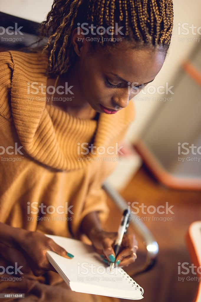Creative African American woman writing in a notebook. stock photo
