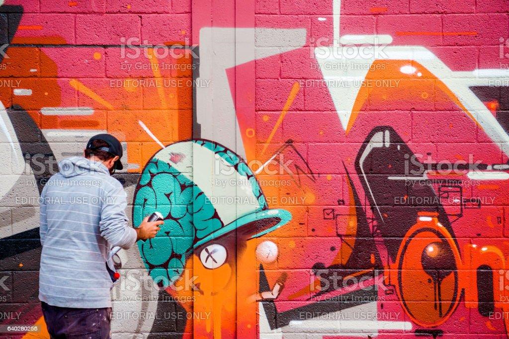 Creative Artist painting graffiti on walls stock photo