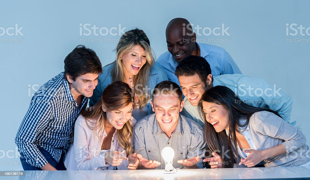 Creative business group looking at a lit light bulb stock photo
