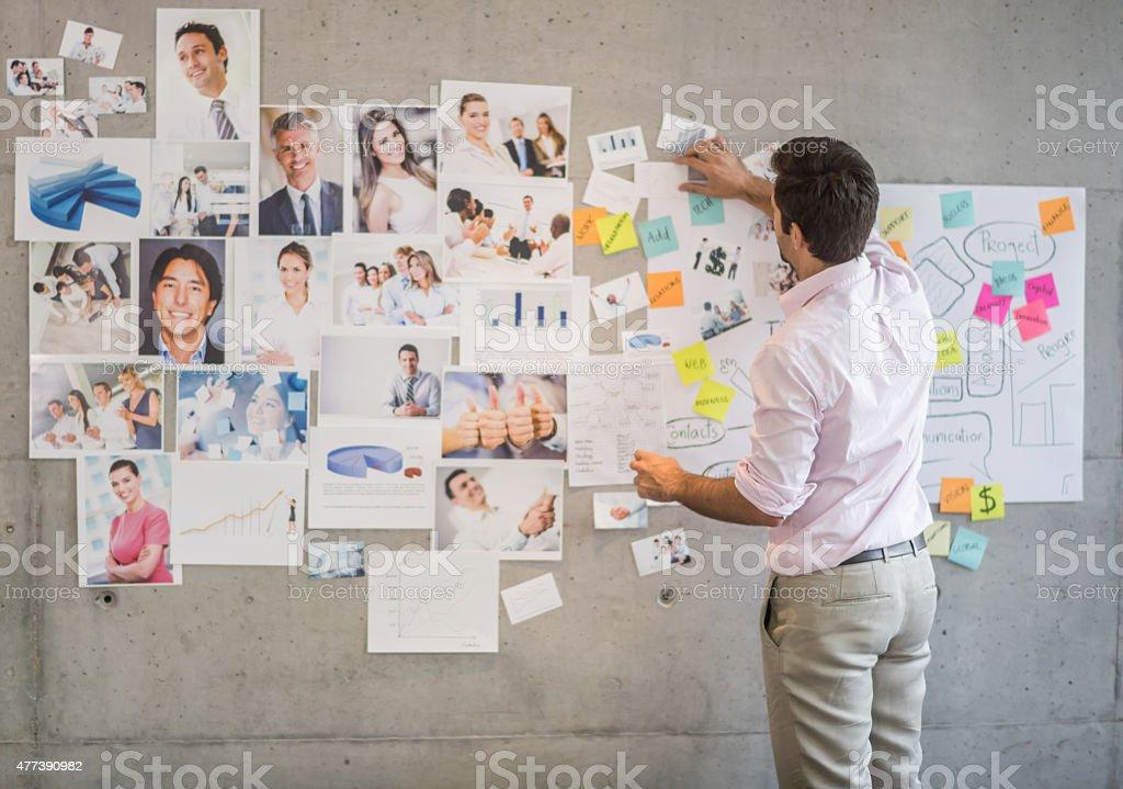 Creative business man creating a wall chart stock photo