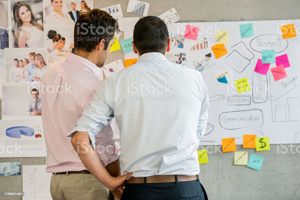 Creative business men looking at a wall chart stock photo
