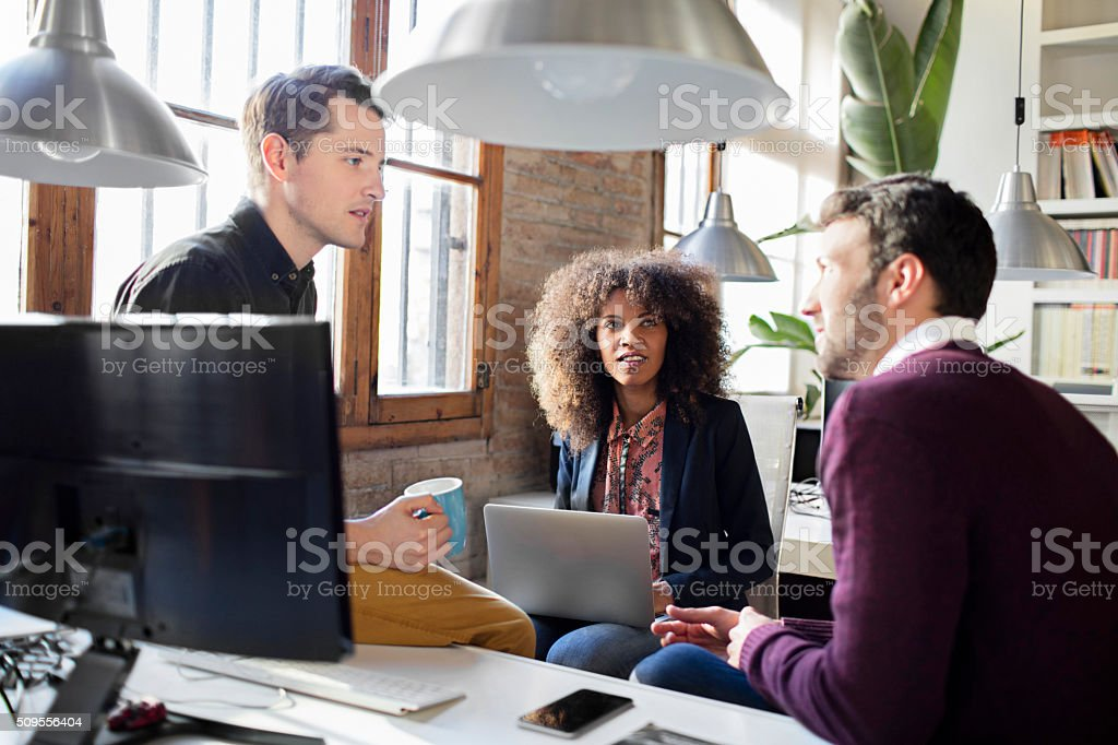 Creative business people having a casual discussion in the office stock photo