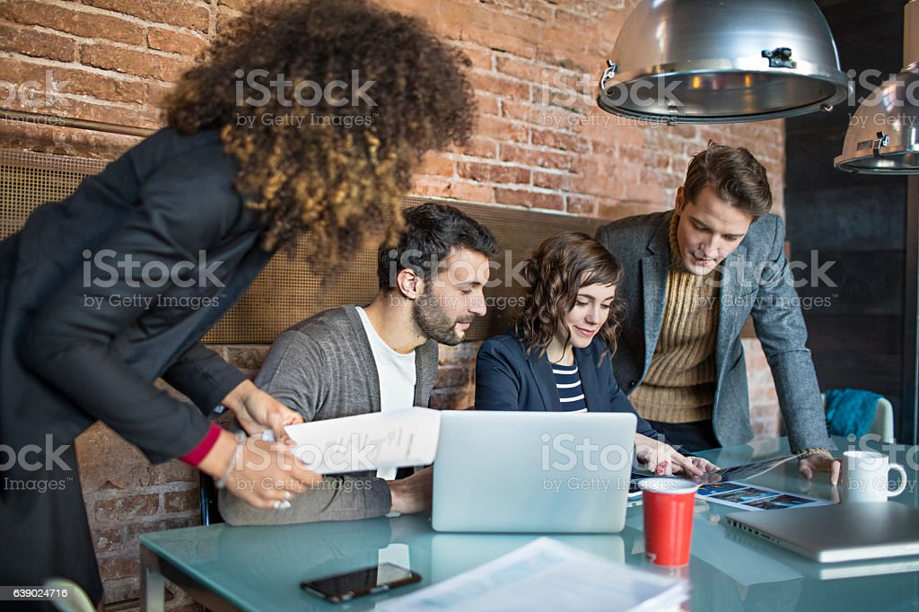 Creative business people having discussion at desk stock photo