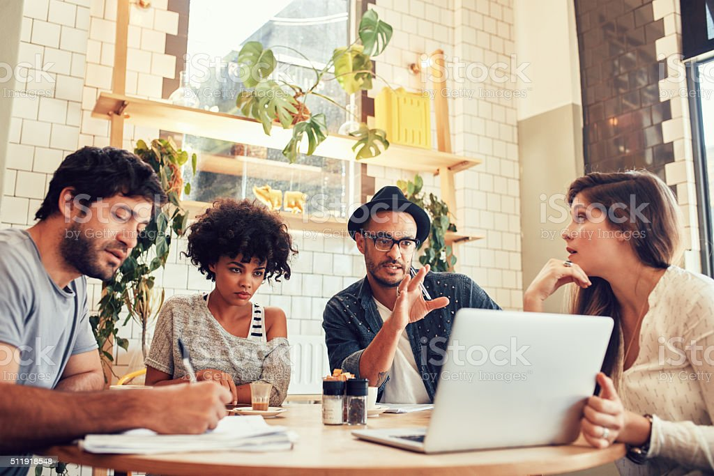 Creative business team at a coffee shop with laptop stock photo