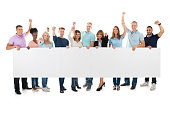Creative Business Team With Arms Raised Holding Blank Billboard