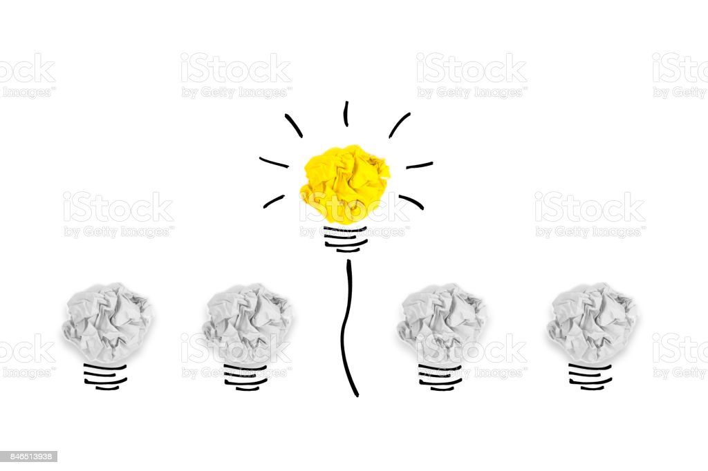 Creative concept. Yellow light bulb outstanding on  bulb crumpled paper on white background stock photo
