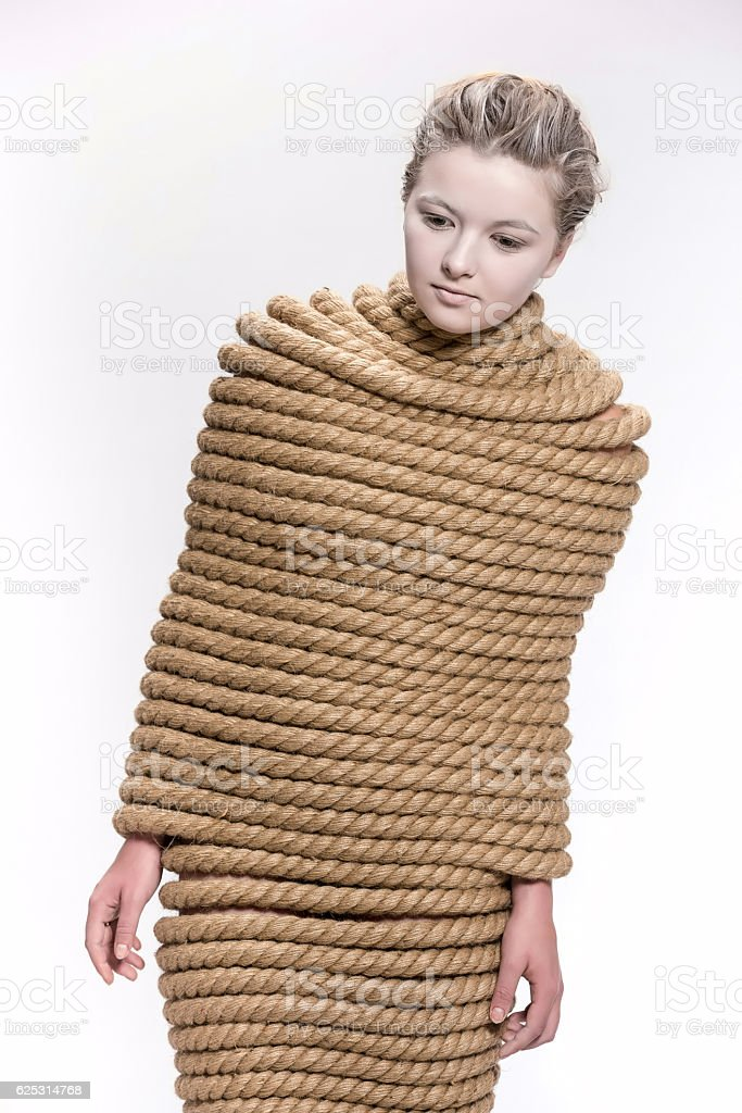 Beautiful young girl model wrapped in hemp rope with on white...