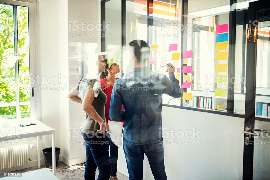 Creative designers discusing in front of glass wall. Startup office stock photo