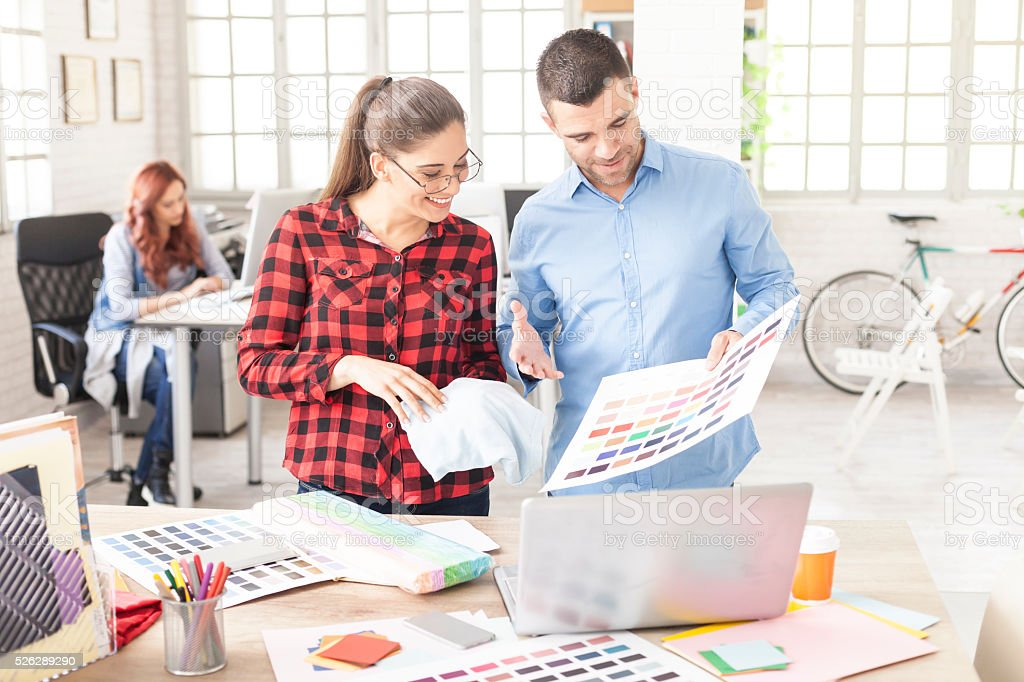 Creative designers holding and looking at color swatchs at workplace stock photo