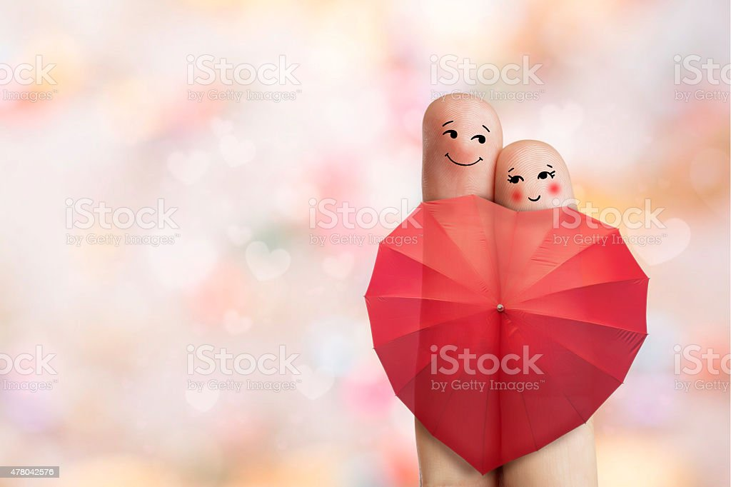 Creative finger art. Lovers are embracing and holding red umbrella. stock photo