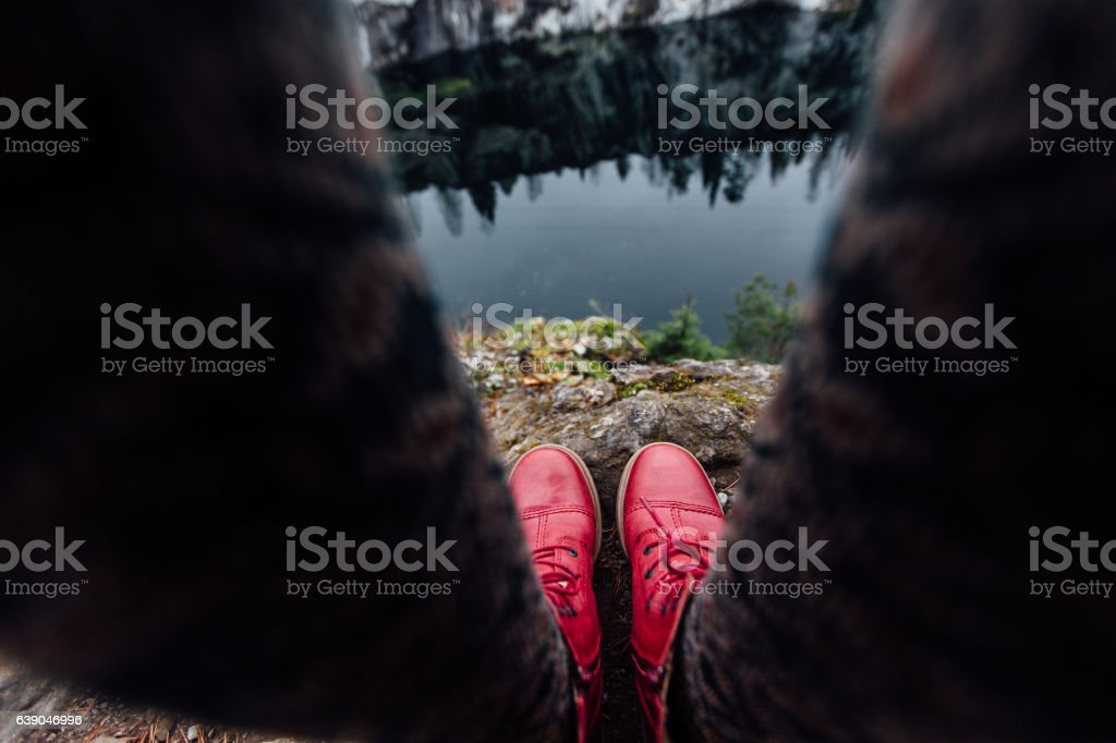 Creative girl standing on the edge of a picturesque cliff stock photo