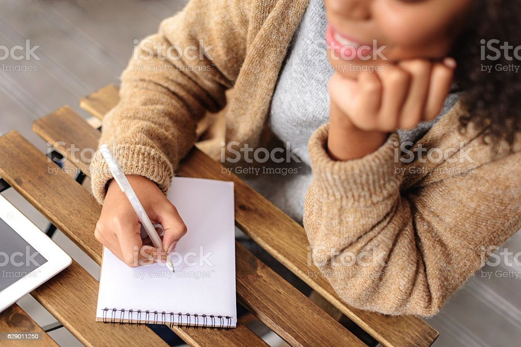 creative girl taking a notes in the notepad stock photo