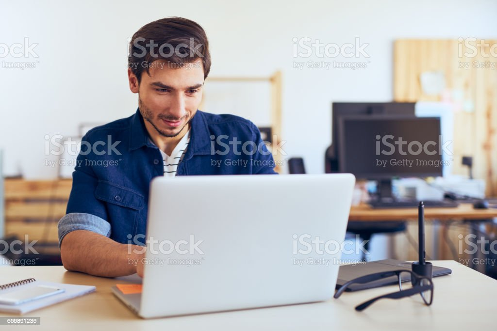 Creative graphic designer working on his laptop at office stock photo