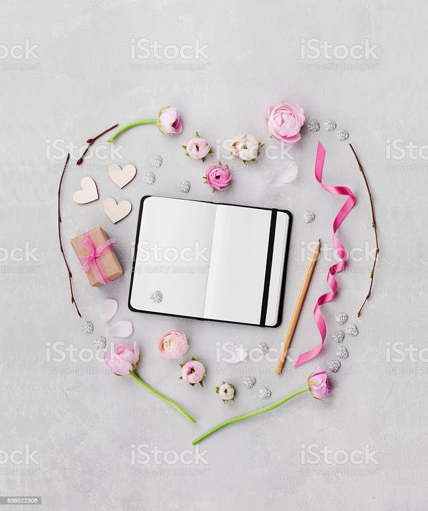 Creative heart from flowers, gift, notebook and decorations. Flat lay. stock photo