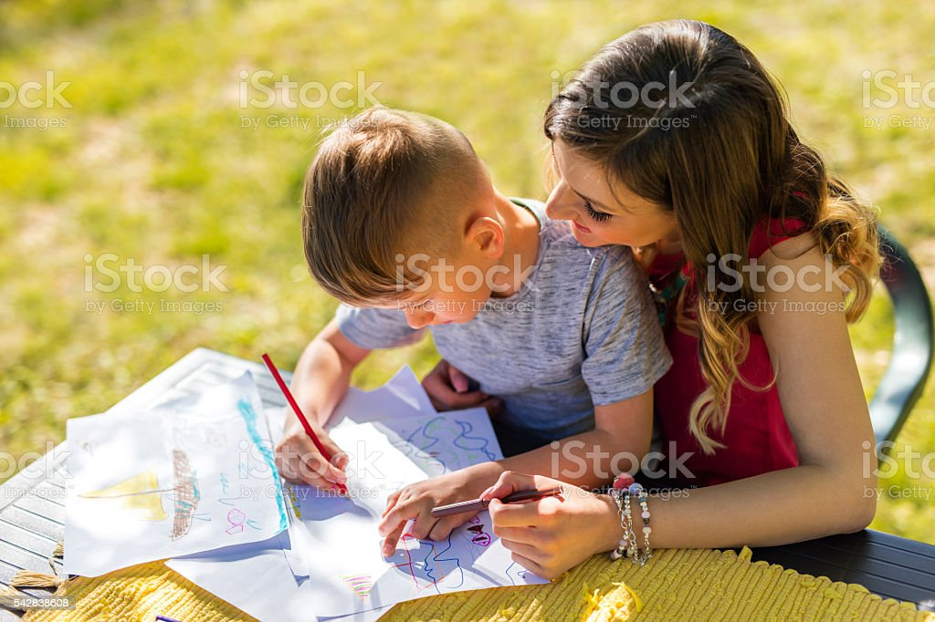 Creative little boy coloring with his mother during springtime. stock photo