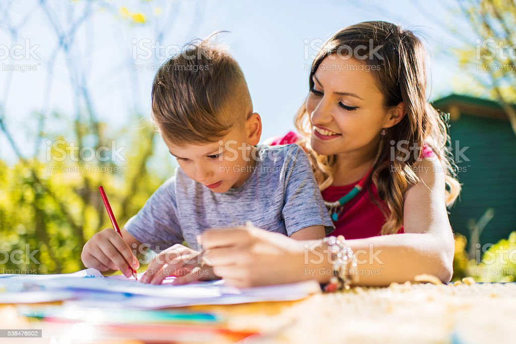 Creative little boy drawing outdoors with his smiling mother. stock photo