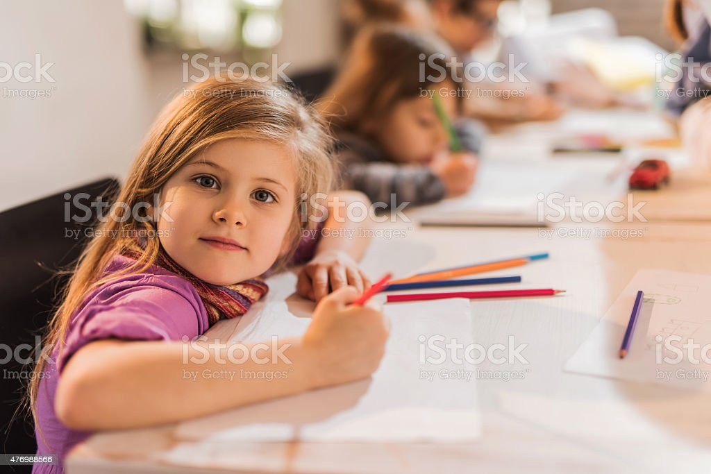 Creative little girl drawing and looking at camera. stock photo