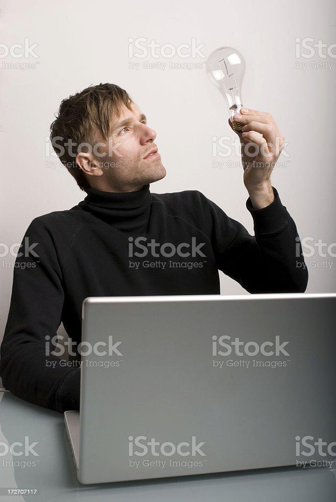 Creative Man in Black Turtleneck Holds Lightbulb royalty-free stock photo