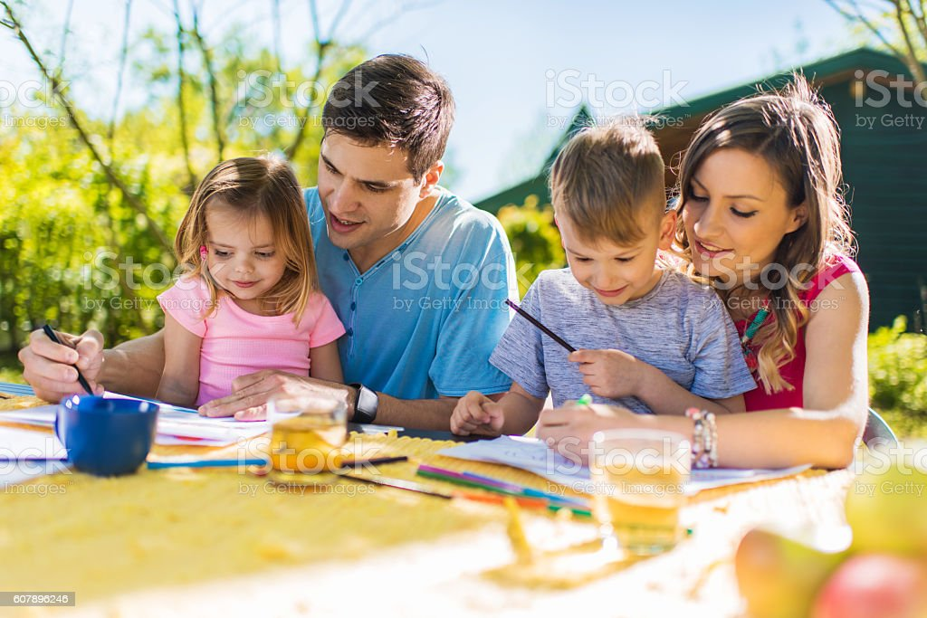 Creative parents drawing with their kids and having fun outdoors. stock photo