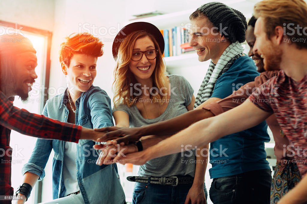 Creative People Joining Hands In Their Office. stock photo