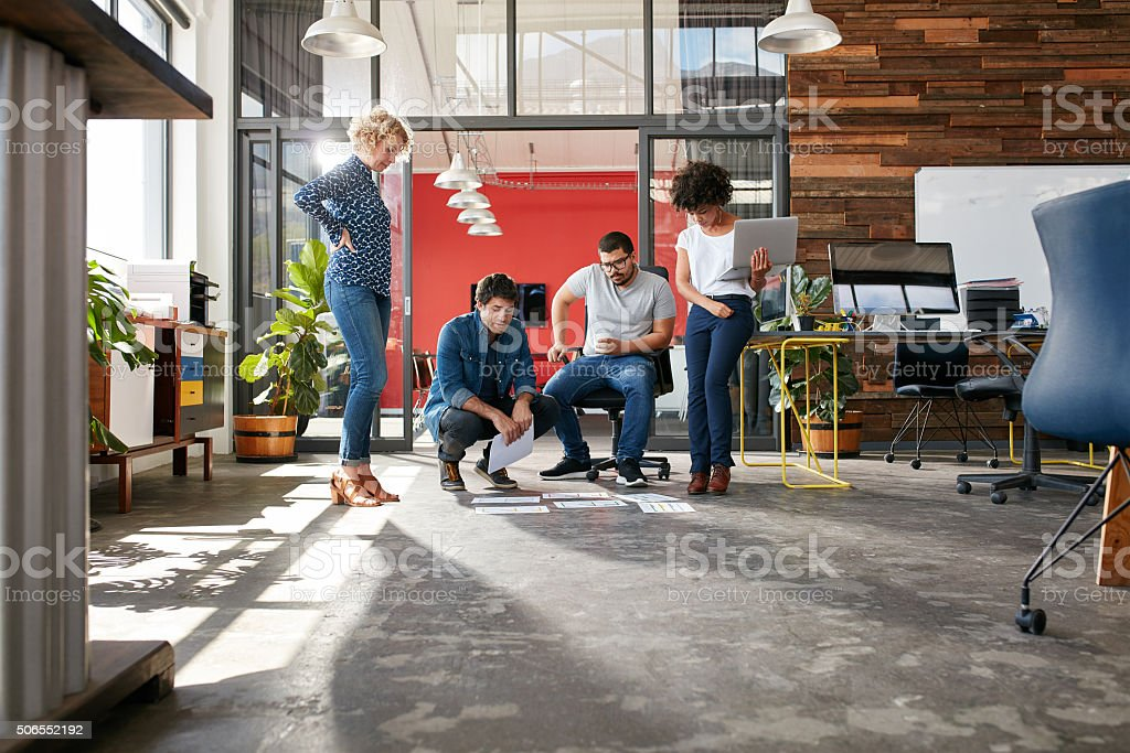 Creative people looking at project plans laying on floor stock photo