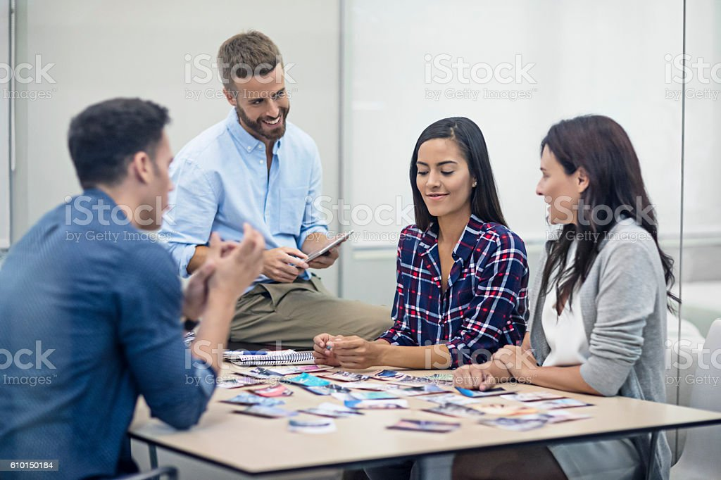 Creative people reviewing picture designs in office meeting stock photo