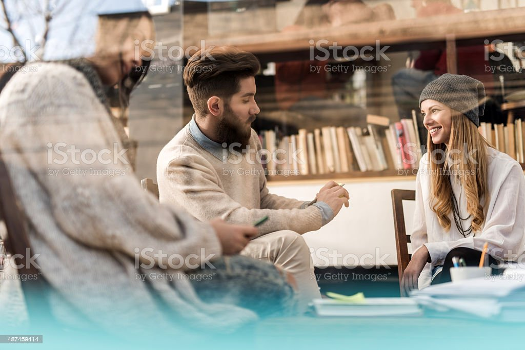 Creative people talking in a cafe. View is through window. stock photo