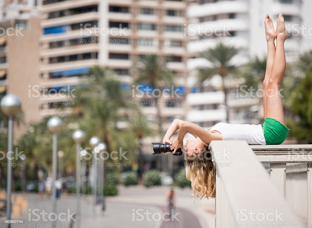 Creative Perspective, Woman taking a Picture over head stock photo