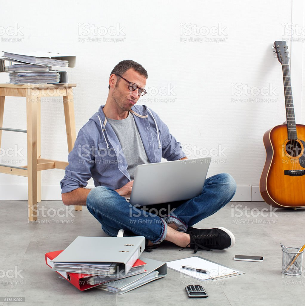 creative start-up entrepreneur working his budget on the floor stock photo
