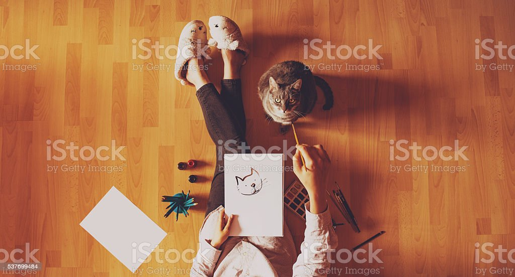 Creative studio: girl drawing her cat. stock photo
