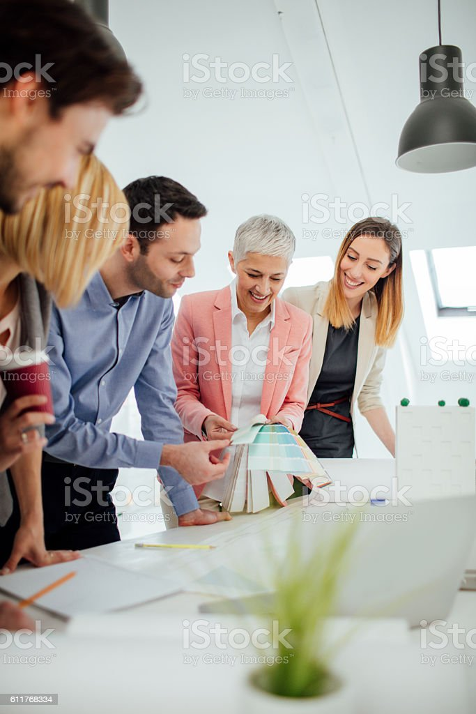 Creative Designers Team examining blueprints and brainstorming in the...
