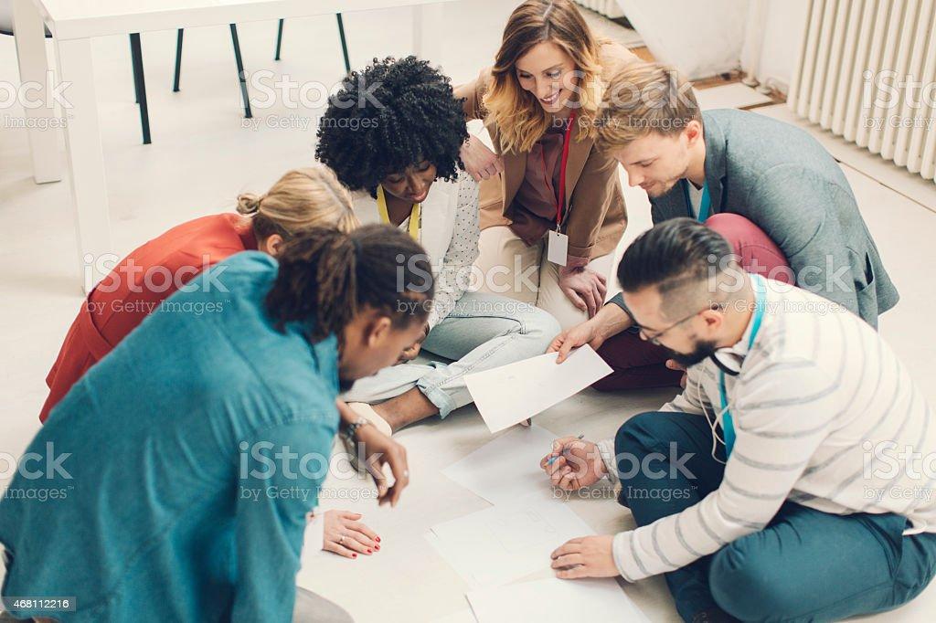 Creative Team Brainstorming On Floor. stock photo