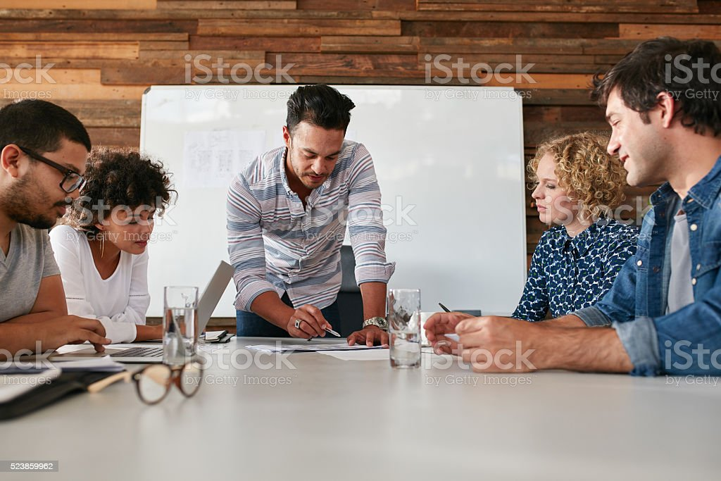 Creative team discussing new ideas on table stock photo