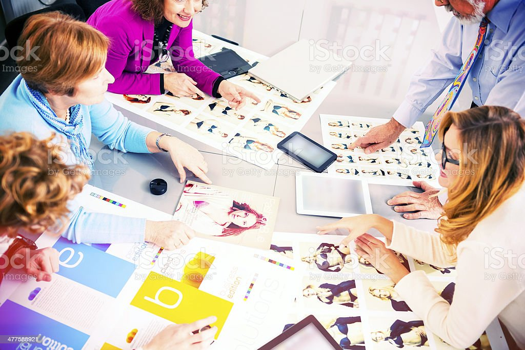 Creative team having a meeting over magazine design stock photo