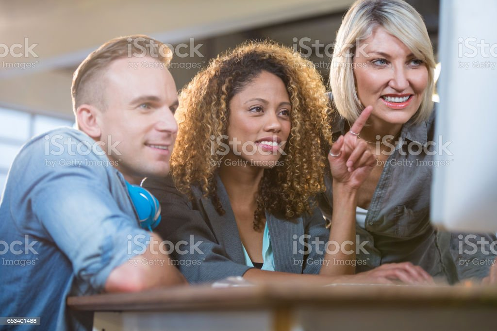 Creative young business people looking at computer stock photo