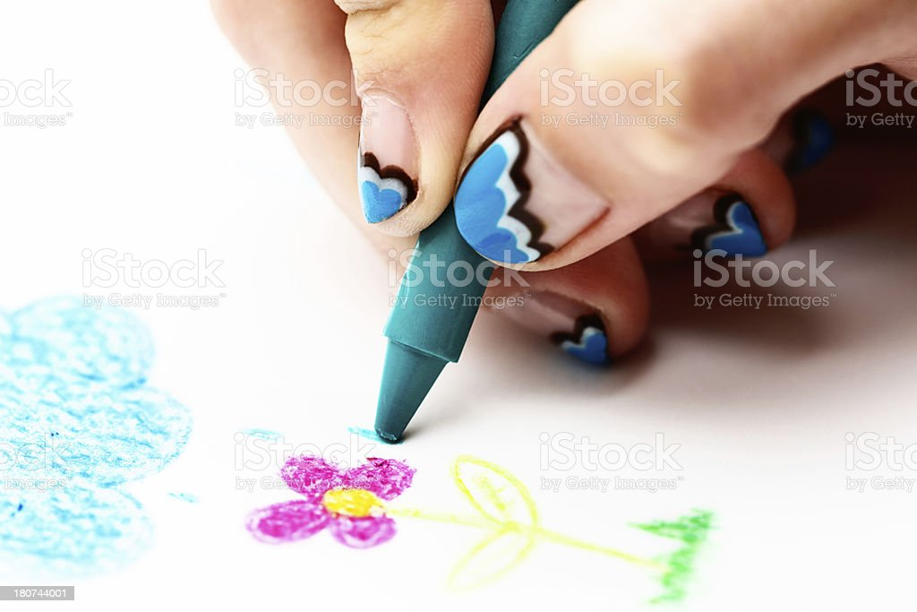 Creatively manicured hand draws with wax crayon in close up royalty-free stock photo