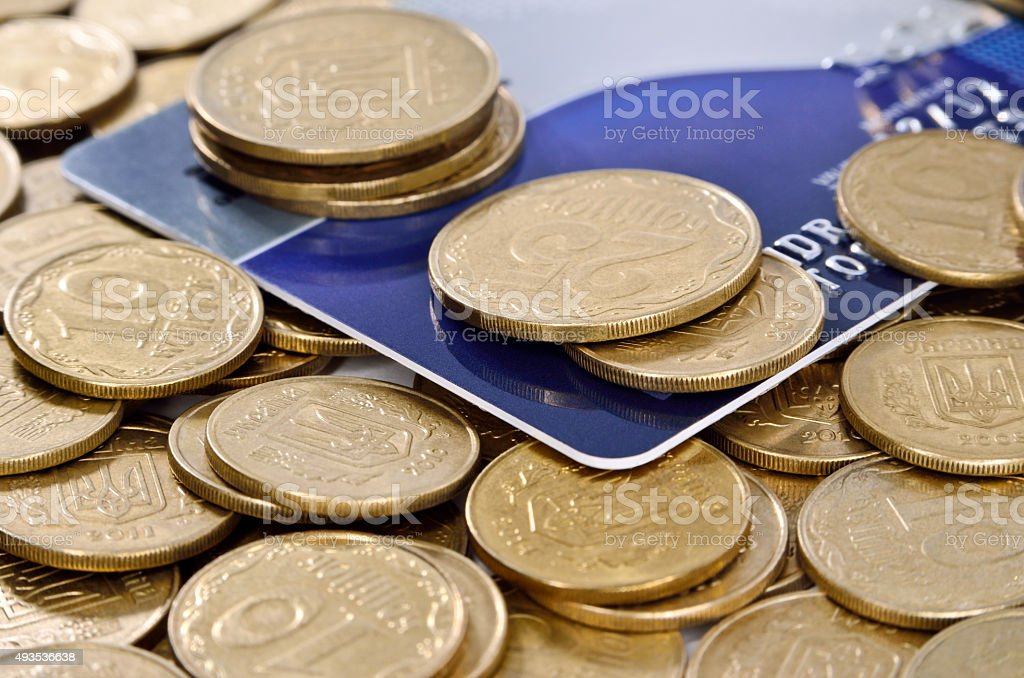 Credit card amongst coins of yellow metal stock photo