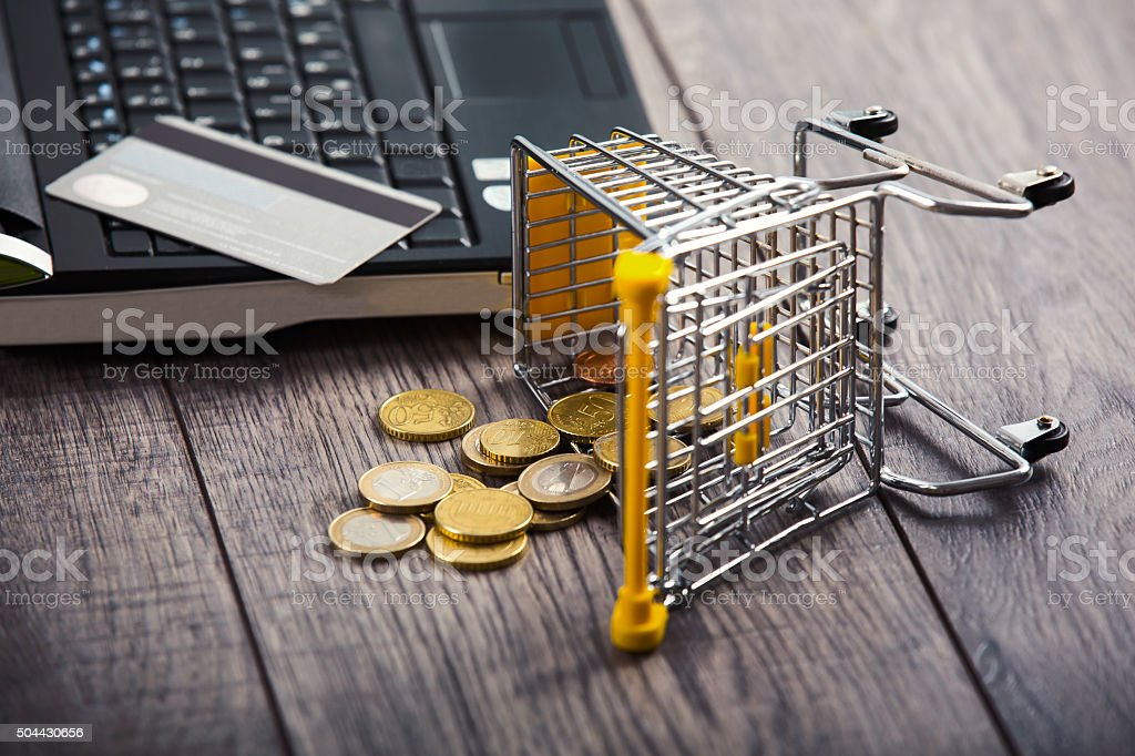 Credit card on a laptop, from supermarket trolleys dropped coins stock photo